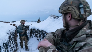 Ukrainian servicemen walk along a snow covered trench guarding their position at the frontline near Vodiane, about 750 kilometers (468 miles) south-east of Kyiv, eastern Ukraine, Saturday, March 5, 2021. . (AP Photo/Evgeniy Maloletka)