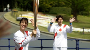 Former Olympian Aya Terakawa, participating as an Olympic torch relay runner, waves as she starts carrying the torch during the first day of the Osaka round at a former Expo site in Suita, north of Osaka, western Japan, Tuesday, April 13, 2021. The Tokyo 2020 Olympic kick-off event which was rescheduled due to the coronavirus outbreak was yet rearranged to hold at the former Expo park, instead of public streets, to close off the audience from the even, following the mayor's decision as Osaka has had sharp increases in daily cases since early March. (AP Photo/Hiro Komae)