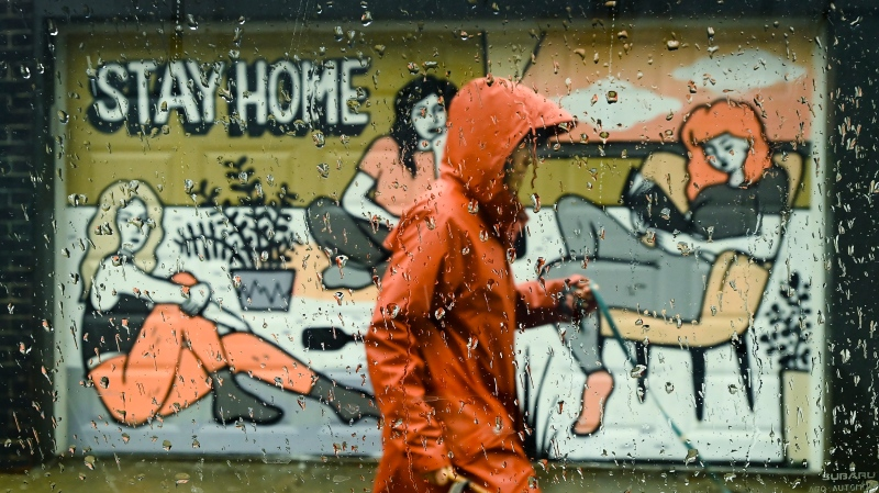 A person walks past a COVID-19 mural designed by artist Emily May Rose on a rainy day during the COVID-19 pandemic in Toronto on Monday, April 12, 2021. THE CANADIAN PRESS/Nathan Denette