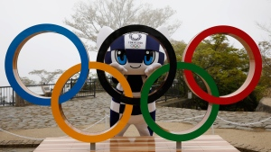 Tokyo 2020 Olympic Games mascot Miraitowa poses with a display of Olympic Symbol after unveiling ceremony of the symbol on Mt. Takao in Hachioji, west of Tokyo, Wednesday, April 14, 2021, to mark 100 days before the start of the Olympic Games. (Kim Kyung-Hoon/Pool)
