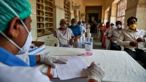 People wait for their turn to be administered COVISHIELD vaccine at a government hospital in Hyderabad, India, Monday, April 12, 2021. With its explosive surge in recent days, India's confirmed infections surpassed Brazil's total Monday as the second-worst hit country. (AP Photo/Mahesh Kumar A.)