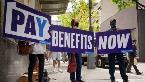 Members of the Mon Valley Unemployed Committee gather on Fifth Avenue in downtown Pittsburgh on Wednesday, April 14, 2021, to demand faster payment for jobless benefits. Some people have been waiting months for a decision on whether they are eligible for benefits, and activists say the state should pay up front to keep people afloat while they wait. (Steve Mellon/Pittsburgh Post-Gazette via AP)