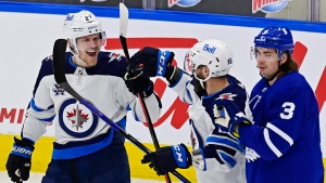 Winnipeg Jets' Nikolaj Ehlers (27) celebrates his goal against the Toronto Maple Leafs with teammate Mathieu Perreault (85) as Maple Leafs' Justin Holl (3) skates past during first period NHL hockey action in Toronto on Thursday, April 15, 2021. THE CANADIAN PRESS/Frank Gunn
