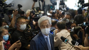 Martin Lee, center, 82-year-old lawyer and former lawmaker, leaves a court after his jail sentences suspended in Hong Kong Friday, April 16, 2021. A Hong Kong court on Friday sentenced five leading pro-democracy advocates, including media tycoon Jimmy Lai, to up to 18 months in prison for organizing a march during the 2019 anti-government protests that triggered an overwhelming crackdown from Beijing. (AP Photo/Vincent Yu)