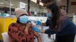 Javeria Jawed, a nursing student for the class of 2021, administers a COVID-19 vaccine to Dularie Disram at the Downsview Arena vaccination site, in Toronto, Friday, April 16, 2021. THE CANADIAN PRESS/Tijana Martin