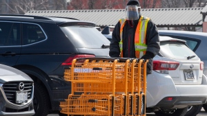 An essential worker gathers shopping carts in a grocery store parking lot in Toronto on Wednesday, March 17, 2021. THE CANADIAN PRESS/Frank Gunn