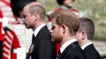 Britain's Prince William, left, and Prince Harry follow the coffin as it slowly makes its way in a ceremonial procession during the funeral of Britain's Prince Philip inside Windsor Castle in Windsor, England, Saturday, April 17, 2021. (Gareth Fuller/Pool via AP)