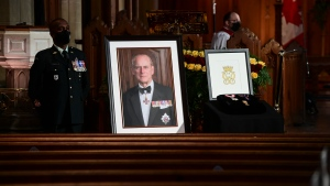 CWO G. Seeloch, left, stands beside a portrait of Prince Philip, A framed drawing of the Duke's cypher and three Canadian medals awarded to the Duke, during the National Commemorative Ceremony in honour of Prince Philip, The Duke of Edinburgh, at Christ Church Cathedral in Ottawa on Saturday, April 17, 2021. THE CANADIAN PRESS/Sean Kilpatrick