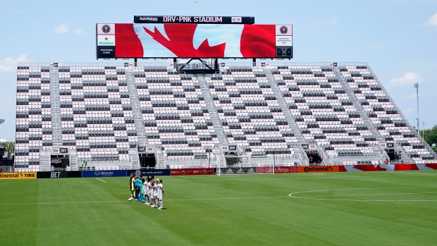 CF Montreal and Toronto FC players stand for the national anthem in a nearly empty DRV PNK Stadium during the first half of an MLS soccer match, Saturday, April 17, 2021, in Fort Lauderdale, Fla. CF Montreal is playing the first part of their season in Inter Miami's stadium due to the coronavirus pandemic. (AP Photo/Lynne Sladky)
