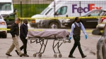 A body is taken from the scene where multiple people were shot at a FedEx Ground facility in Indianapolis, Friday, April 16, 2021. A gunman killed several people and wounded others before taking his own life in a late-night attack at a FedEx facility near the Indianapolis airport, police said.  (AP Photo/Michael Conroy)