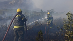 Firefighters fight a raging fire on the slopes of Table Mountain, in Cape Town South Africa, Monday, April 19, 2021. Residents were evacuated from Cape Town neighborhoods Monday as a huge fire spreading on the slopes of the city's famed Table Mountain was fanned by strong winds overnight and houses came under threat. (AP Photo)