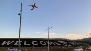 "A giant sign painted near the main runway of the Wellington International Airport greets travelers returning home in Wellington, New Zealand Monday, April 19, 2021. The sign reads ""Welcome Whanau"" with the second word an Indigenous Maori word meaning family. The start of quarantine-free travel was a relief for families who have been separated by the coronavirus pandemic as well as to struggling tourist operators. (AP Photo/Nick Perry)"