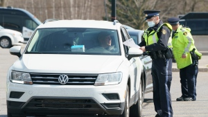 Motorists are screened at a police check point to limit non-essential travel from Quebec at the entrance of the province of Ontario on Highway 401 near Bainsville, Ont. on Monday, April 19, 2021. THE CANADIAN PRESS/Paul Chiasson