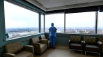 Registered nurse Stephanie Flores, who has been redeployed from the operating room to the intensive care unit, looks out the window in the ICU at the Humber River Hospital during the COVID-19 pandemic in Toronto on Tuesday, April 13, 2021. THE CANADIAN PRESS/Nathan Denette