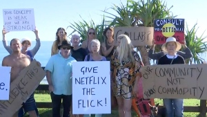 "In this image made from video, protesters display placards at Byron Bay, Australia, Tuesday, April 20, 2021. Angry Byron Bay locals are protesting the filming of a reality television series that some fear will damage the reputation of their trendy Australian tourist town. Netflix says its first Australian reality series would ""aim to build a connection between the people we meet in the show and the audience."" (Australian Broadcasting Corporation via AP)"