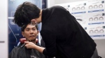 Yoshihiro Kamichi, a 44-year-old office worker, receives makeup and gets his hair done by a makeup artist at Ikemen-Works, a makeup salon for men, in Tokyo Wednesday, Feb. 3, 2021. The coronavirus pandemic has been pushing businesses to the edge in Japan, but some in the men's beauty industry have seen an unexpected expansion in their customer base. Japanese businessmen in their 40s, 50s and 60s who had little interest in cosmetics before the pandemic are now buying makeup. (AP Photo/Eugene Hoshiko)