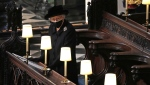 Britain's Queen Elizabeth II takes her seat alone in St. George's Chapel during the funeral of Prince Philip, the man who had been by her side for 73 years, at Windsor Castle, Windsor, England, Saturday April 17, 2021. Prince Philip died April 9 at the age of 99 after 73 years of marriage to Britain's Queen Elizabeth II. (Yui Mok/Pool via AP)