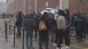 People lineup outside in the snow for a COVID-19 vaccine at a pop-up clinic outside Downsview Arena.