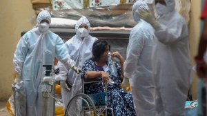 Health workers attend to a patient at the Jumbo COVID-19 hospital in Mumbai, India, Thursday, April 22, 2021. New infections are rising faster in India than any other place in the world, stunning authorities and capsizing its fragile health system. (AP Photo/Rafiq Maqbool)
