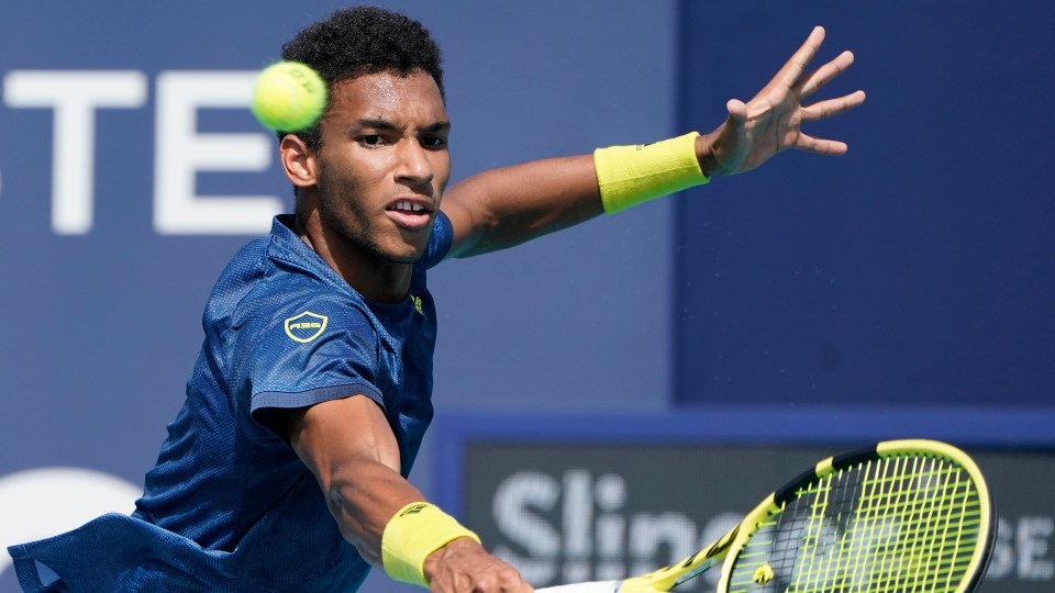 Felix Auger-Aliassime of Canada returns to John Isner during the Miami Open tennis tournament, Sunday, March 28, 2021, in Miami Gardens, Fla. (AP Photo/Marta Lavandier)
