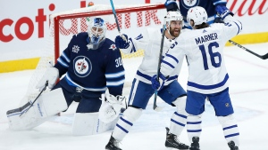 Toronto Maple Leafs' Nick Foligno (71) and Mitchell Marner (16) celebrate Marner's goal on Winnipeg Jets goaltender Laurent Brossoit (30) during second period NHL action in Winnipeg on Thursday, April 22, 2021. THE CANADIAN PRESS/John Woods