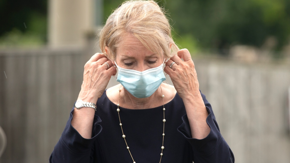 Dr. Merrilee Fullerton, Ontario's Minister of Long-Term Care, removes her mask before taking a question from the media during an announcement in Ajax, Ont., on Tuesday, July 28, 2020. THE CANADIAN PRESS/Chris Young