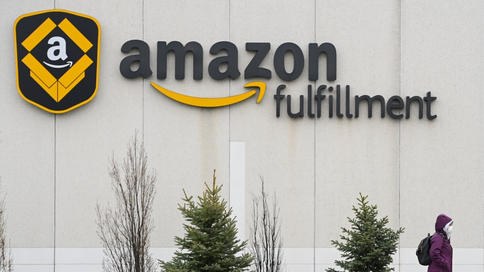 A person walks past an Amazon Fulfillment Centre during the COVID-19 pandemic in Brampton, Ont., Tuesday, April 20, 2021. Peel and Toronto will close businesses with five or more COVID-19 cases linked to the workplace under new guidelines to help curb the spread. THE CANADIAN PRESS/Nathan Denette
