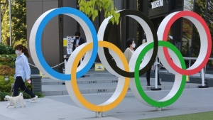A woman with her dog walks past the Olympic rings in Tokyo, Tuesday, April 20, 2021. (AP Photo/Koji Sasahara)