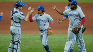 Toronto Blue Jays catcher Danny Jansen, left, celebrates with third baseman Santiago Espinal, center, and first baseman Vladimir Guerrero Jr., right, after closing out the Tampa Bay Rays during the ninth inning of a baseball game Sunday, April 25, 2021, in St. Petersburg, Fla. (AP Photo/Chris O'Meara)