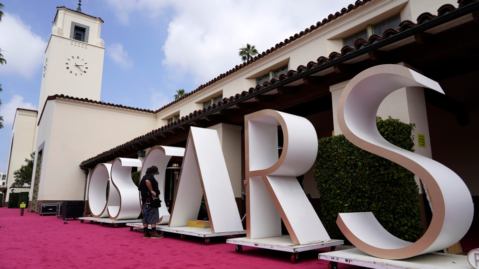 An Academy Awards crew member looks over a background element for the red carpet at Union Station, one of the locations for Sunday's 93rd Academy Awards, Saturday, April 24, 2021, in Los Angeles. (AP Photo/Chris Pizzello, Pool)
