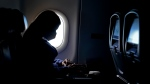 FILE - In this Wednesday, Feb. 3, 2021, file photo, a passenger wears a face mask she travels after take off from Hartsfield-Jackson International Airport in Atlanta. (AP Photo/Charlie Riedel, File)