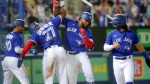 Toronto Blue Jays' Vladimir Guerrero Jr. (27) congratulates Teoscar Hernandez on his three-run home run as Marcus Semien (10) and Bo Bichette celebrate against the Atlanta Braves during the sixth inning of a baseball game Friday, April 30, 2021, in Dunedin, Fla. (AP Photo/Mike Carlson)