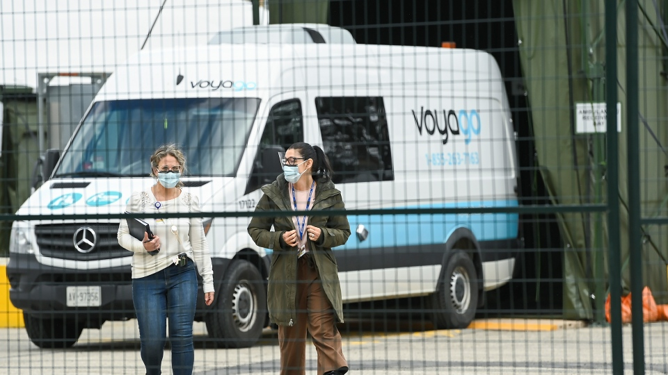 A hospital transfer van unloads a COVID-19 patient at a mobile health unit at Sunnybrook Hospital during the COVID-19 pandemic in Toronto on Friday, April 30, 2021. THE CANADIAN PRESS/Nathan Denette