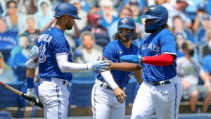 Toronto Blue Jays' Lourdes Gurriel Jr., left, congratulates Bo Bichette and Vladimir Guerrero Jr. after they scored on a double by Marcus Semien against the Atlanta Braves during the third inning of a baseball game Sunday, May 2, 2021, in Dunedin, Fla. (AP Photo/Mike Carlson)