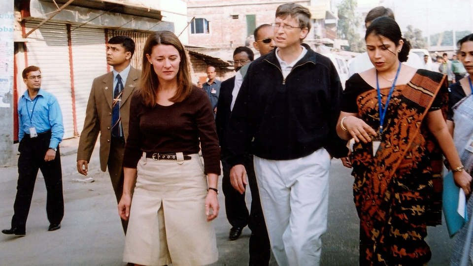 In this Dec. 5, 2005, file photo, Bill Gates, founder and chairman of Microsoft Corp., center, and his wife Melinda, left, walk on a street in Dhaka, Bangladesh. The couple announced Monday, May 3, 2021, that they are divorcing. The Microsoft co-founder and his wife, with whom he launched the world's largest charitable foundation, said they would continue to work together at The Bill & Melinda Gates Foundation. (AP Photo/Gazi Sarwar, File)