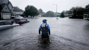 In this Sunday, Sept. 16, 2018 file photo, a member of the North Carolina Task Force urban search and rescue team wades through a flooded neighborhood looking for residents who stayed behind as Florence continues to dump heavy rain in Fayetteville, N.C. According to data released by the National Oceanic and Atmospheric Administration on Tuesday, May 4, 2021, the new United States normal is not just hotter, but wetter in the eastern and central parts of the nation and considerably drier in the West than just a decade earlier. (AP Photo/David Goldman)