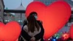 A couple hugs as they stand among lit heart shaped balloons on Chinese Valentine's Day which coincides with the third day of the Chinese Lunar New Year in Beijing on Sunday, Feb. 14, 2021. (AP Photo/Ng Han Guan)