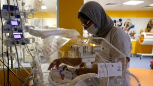 A Moroccan nurse takes care of one of the nine babies protected in an incubator at the maternity ward of the private clinic of Ain Borja in Casablanca, Morocco, Wednesday, May 5, 2021. (AP Photo / Abdeljalil Bounhar)