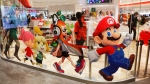 In this Jan. 23, 2020, file photo, Nintendo characters, including Mario, right, are seen on a glass of its official store in Tokyo. (AP Photo/Jae C. Hong, File)