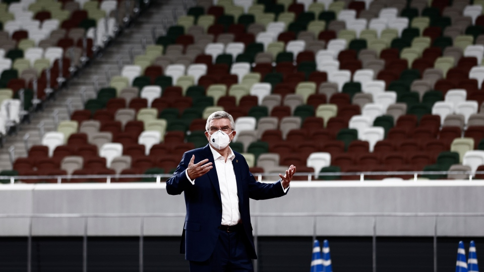 IOC President Thomas Bach wearing a face mask gestures during a visit to the National Stadium, the main venue for the 2020 Olympic and Paralympic Games postponed until July 2021 due to the coronavirus pandemic, in Tokyo Tuesday, Nov. 17, 2020.(Behrouz Mehri/Pool Photo via AP)