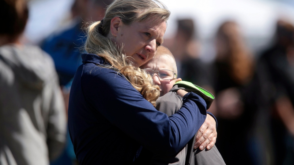 People embrace after a school shooting at Rigby Middle School in Rigby, Idaho, Thursday, May 6, 2021. A shooting at the eastern Idaho middle school Thursday injured two students and a custodian, and a male student has been taken into custody, authorities said. (John Roark/The Idaho Post-Register via AP)