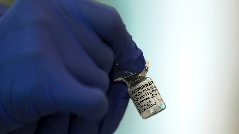 A medical worker holds a Pfizer-BioNTech COVID-19 vaccine at Tokyo Medical Center in Tokyo Wednesday, Feb. 17, 2021. (Behrouz Mehri/Pool Photo via AP)
