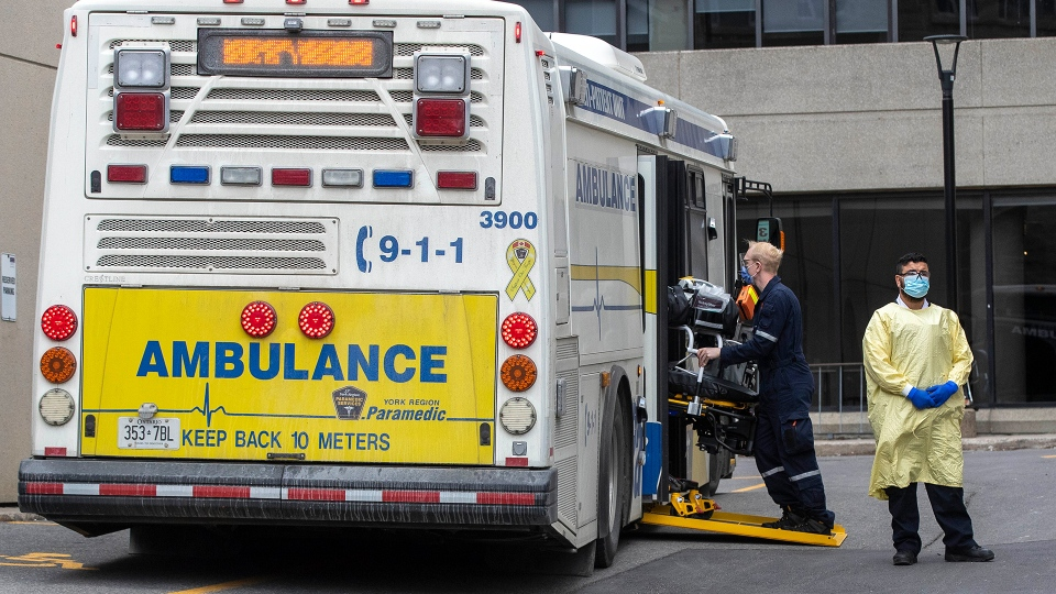 Paramedics walk back gurneys to the multi-patient transport at Kingston General Hospital after dropping off COVID-19 patients from the GTA area, in Kingston, Ont., on Thursday Apr. 22, 2021. THE CANADIAN PRESS/Lars Hagberg