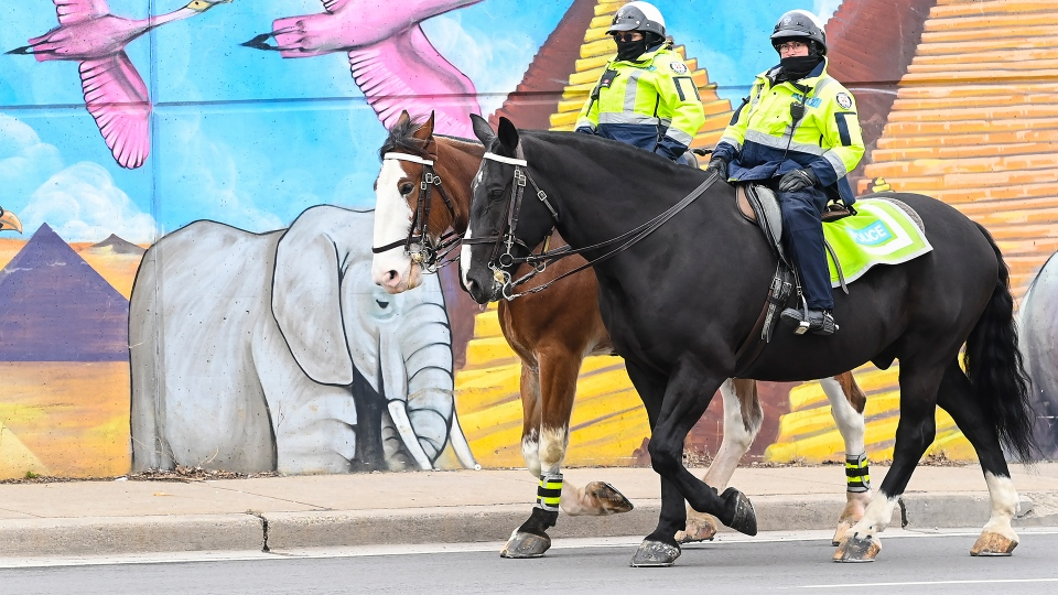 Police officers ride their horses past a mural on Earth Day during the COVID-19 pandemic in Toronto on Thursday, April 22, 2021. THE CANADIAN PRESS/Nathan Denette
