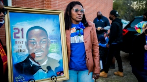 Wanda Cooper-Jones, the mother of Ahmaud Arbery, stands with a painting of her son during a candlelight vigil in his honor at New Springfield Baptist Church in Waynesboro, Ga., Tuesday, Feb. 23, 2021. The event marks the fist anniversary of his death. (Michael Holahan/The Augusta Chronicle via AP)