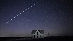 File-In this photo taken May 6, 2021, with a long exposure, a string of SpaceX StarLink satellites passes over an old stone house near Florence, Kan. The train of lights was actually a series of relatively low-flying satellites launched by Elon Musk's SpaceX as part of its Starlink internet service earlier this week. (AP Photo/Reed Hoffmann, File)