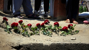People puts flowers outside a school after a deadly attack on Saturday, in Kabul, Afghanistan, Sunday, May 9, 2021. The Interior Ministry said Sunday that the death toll in the horrific bombing at the entrance to the girls' school in the Afghan capital has soared to some 50 people, many of them pupils between 11 and 15 years old, and the number of wounded in Saturday's attack has also climbed to more than 100. (AP Photo/Mariam Zuhaib)