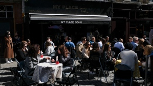 People sit at set up tables outside a restaurant in Soho, in London, Saturday, April 17, 2021, as shops, gyms, hairdressers, restaurant patios and beer gardens reopened Monday after months of lockdown. (AP Photo/Alberto Pezzali)