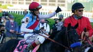 Jockey John Velazquez onboard Medina Spirit gives a thumbs up after winning the 147th running of the Kentucky Derby at Churchill Downs, Saturday, May 1, 2021, in Louisville, Ky. (AP Photo/Brynn Anderson)