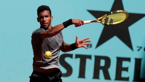 Felix Auger-Aliassime of Canada returns the ball to Casper Rudd of Norway during their match at the Madrid Open tennis tournament in Madrid, Spain, Tuesday, May 4, 2021. (AP Photo/Paul White)